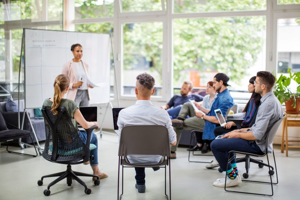Photo of a group of people sitting on chairs in a circle, with one person standing in front of a white board