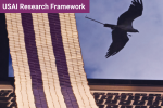 photo of a laptop with a beaded belt draped over the screen and keyboard, displaying a flying eagle on the screen