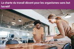 """Image title says, """"La charte du travail décent pour les organismes sans but lucratif."""" It's an image of two workers in a meeting room pointing at a paper on the table."""